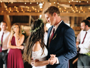 Newly wed couple dancing in a rustic bar decorated with lights and flowers